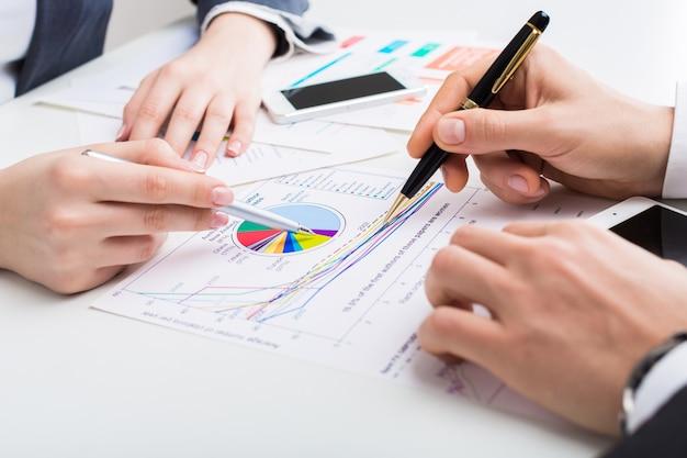Geschäftsleute, die am tisch bericht mit diagrammen auf weiß erstellen