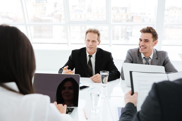 Geschäftsleute, die am tisch sitzen und bei einem meeting im konferenzraum interagieren