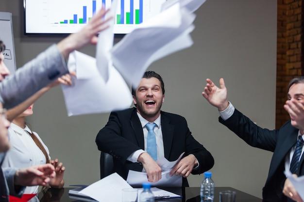Geschäftsleute, die am tisch sitzen und papiere werfen und lachen.