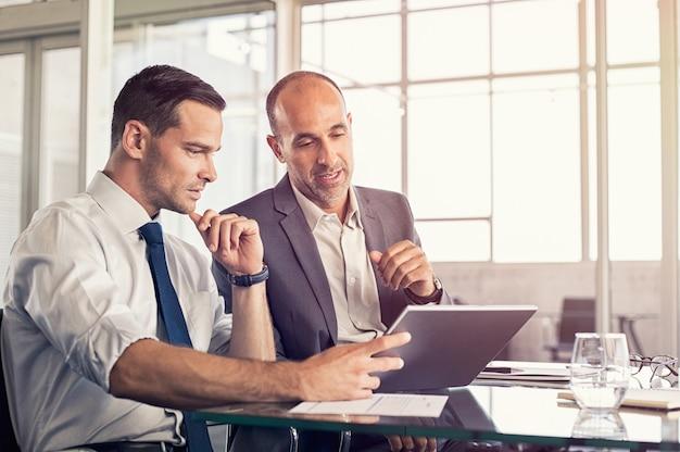 Geschäftsleute, die an digitalem tablet arbeiten