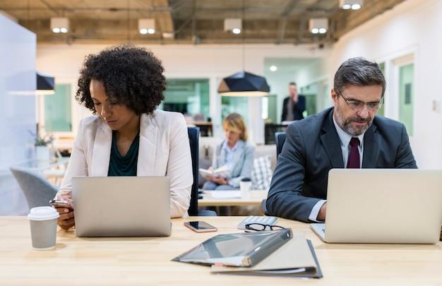 Geschäftsleute, die an digitalen geräten arbeiten