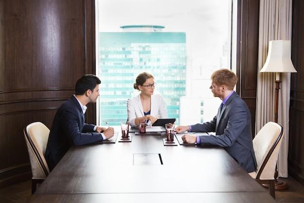 Geschäftsleute, die an einem großen holztisch sitzt mit einem laptop