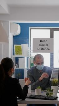Geschäftsleute, die an finanzdiagrammen mit digitalem tablet arbeiten, während sie am schreibtisch in einer unternehmensgesellschaft sitzen corporate