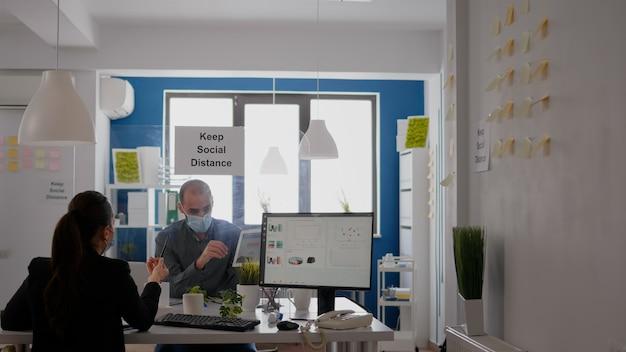 Geschäftsleute, die an finanzdiagrammen mit digitalem tablet arbeiten, während sie am schreibtisch in einer unternehmensgesellschaft sitzen. team, das gesichtsmasken trägt, hält soziale distanz ein, um eine coronavirus-pandemie zu vermeiden
