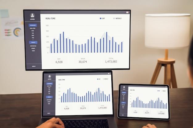 Geschäftsleute, die an laptops arbeiten und statistikdiagramme mit den computerbildschirmen und dem tablet auf dem schreibtisch anzeigen.