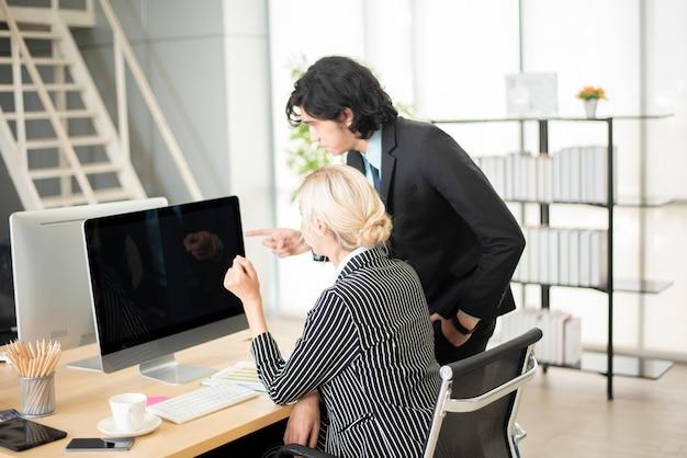 Geschäftsleute, die auf computerbildschirm zeigen