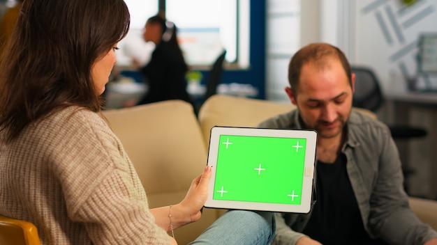 Geschäftsleute, die auf der couch sitzen und finanzstatistiken analysieren, tablet mit grünem bildschirm halten, während ein vielfältiges team am hintergrund arbeitet. multiethnische mitarbeiter planen projekt auf chroma-key-display