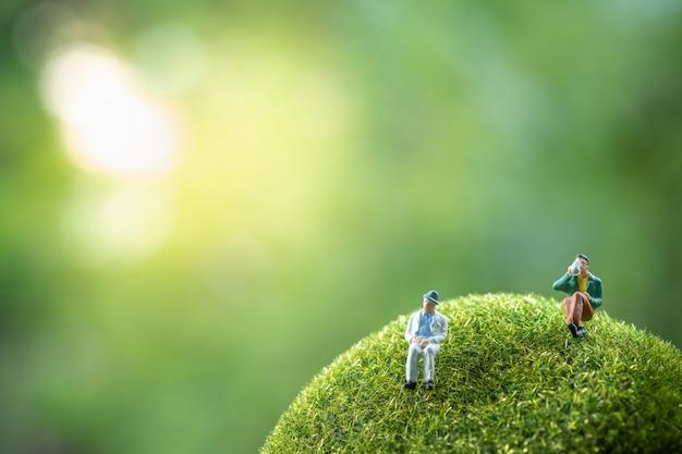 Geschäftsleute, die auf einem grünen moosstein sitzen.