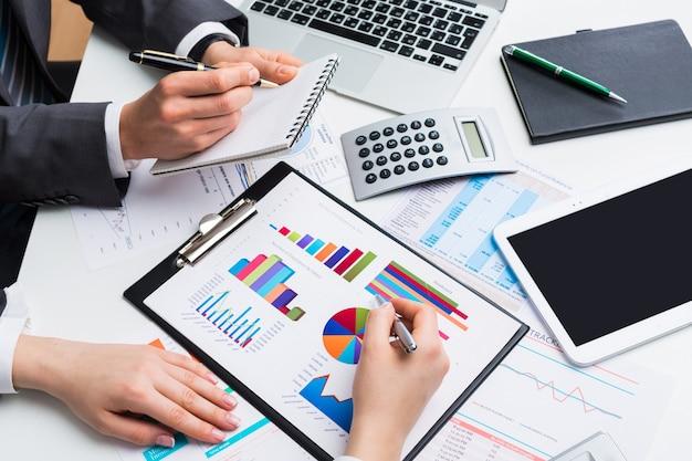 Geschäftsleute, die auf rechner zählen, die am tisch sitzen.