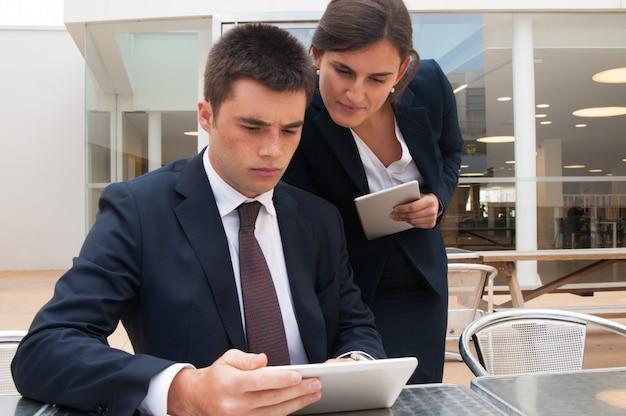 Geschäftsleute, die auf tabletten grasen und bei tisch nachrichten lesen