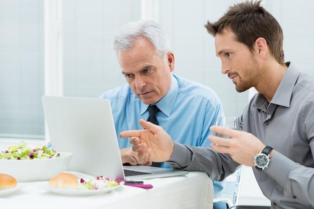Geschäftsleute, die beim mittagessen arbeiten