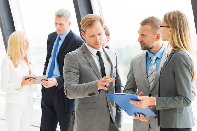 Geschäftsleute, die beim treffen im büro nahe fenster sprechen