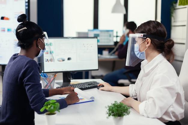 Geschäftsleute, die computer mit finanzgrafik verwenden, die gesichtsmaske für covid19 tragen. multiethnisches team, das in unternehmen mit neuer normalität arbeitet, die die soziale distanz während der globalen pandemie mit coronaviren respektiert