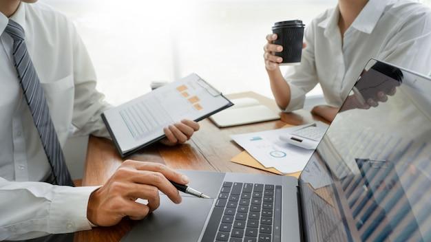 Geschäftsleute, die das besprechen mit der mitarbeiterplanung analysiert finanzdokumentdatendiagramme sprechen