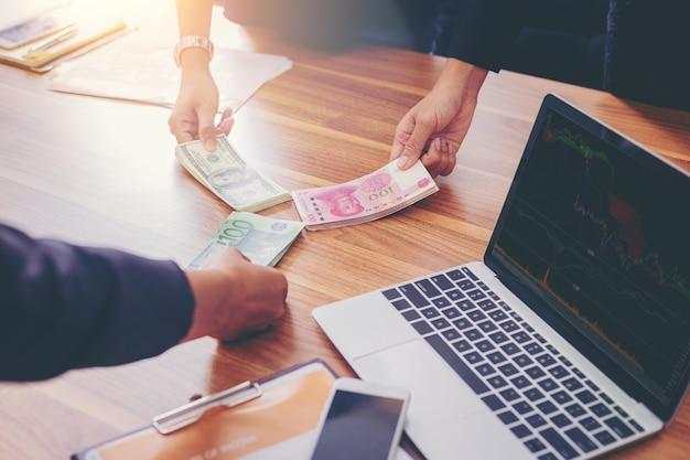 Geschäftsleute, die das geld teilen für austauschinvestitionen halten