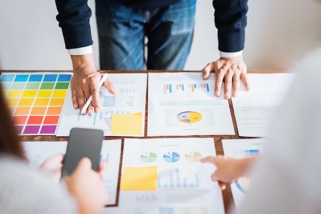 Geschäftsleute, die das team arbeitet an hölzernem schreibtisch- und handmann zeigt auf finanzdokumente im büro treffen. strategie für erfolgreiche besprechungsarbeitsplätze.