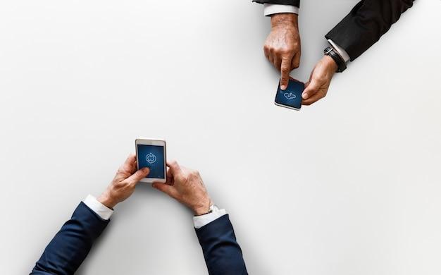 Geschäftsleute, die daten durch das handy lokalisiert auf weißem hintergrund synchronisieren