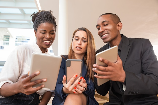Geschäftsleute, die dem verwirrten kollegen video oder fotos zeigen