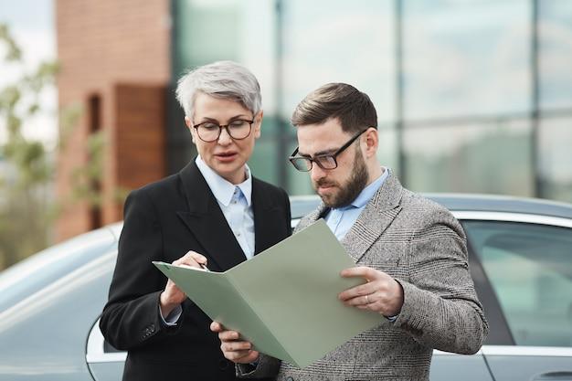 Geschäftsleute, die den vertrag zusammen prüfen, während sie draußen in der stadt stehen