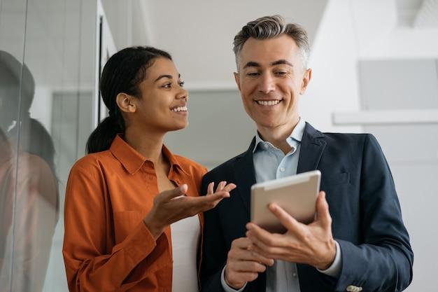 Geschäftsleute, die die planung digitaler tablets verwenden, starten und tauschen ideen am arbeitsplatz aus.