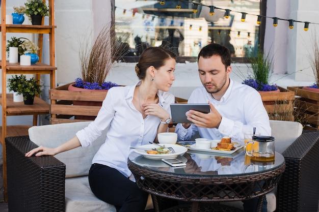 Geschäftsleute, die digitale tablette im café während eines treffens betrachten