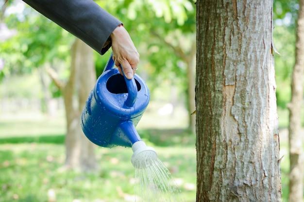Geschäftsleute, die dosen mit gießpflanzen halten, um bäume wachsen zu lassen und stärker zu werden.