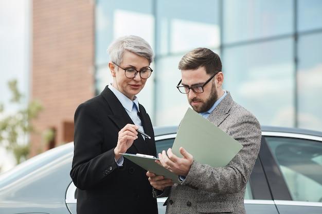 Geschäftsleute, die draußen stehen, lesen vertrag zusammen und diskutieren ihn