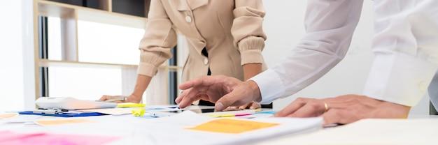 Geschäftsleute, die ein startprojekt planen, platzieren eine haftnotizsitzung, um ihre idee zu teilen