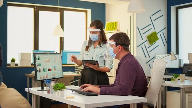 Geschäftsleute, die eine schutzmaske in einem neuen normalen büro tragen, machen eine finanzstrategie, die auf den desktop zeigt und notizen auf dem tablet macht. multiethnisches team, das in unternehmen arbeitet und die soziale distanz respektiert.