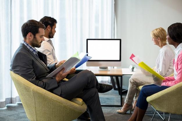 Geschäftsleute, die einen bildschirm während einer videokonferenz betrachten