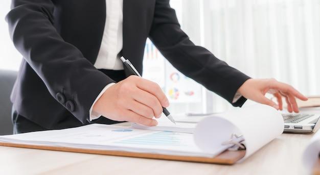 Geschäftsleute, die einen bleistift unter hinweis darauf, über laptop
