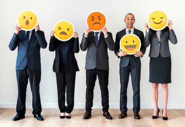 Geschäftsleute, die emoji ikonen stehen und halten
