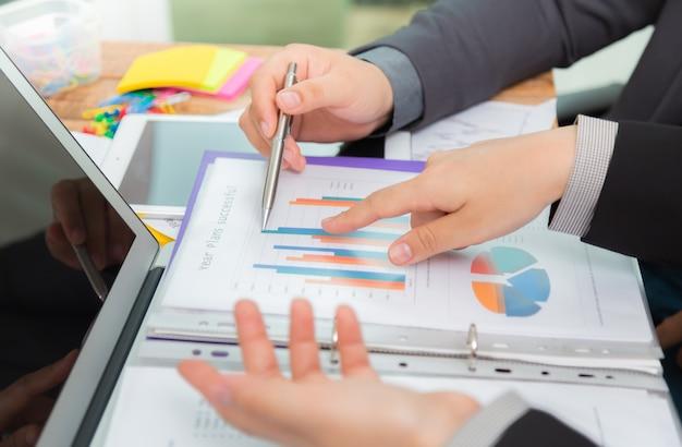 Geschäftsleute, die ergebnisse eines graphen in einem büro zu vergleichen