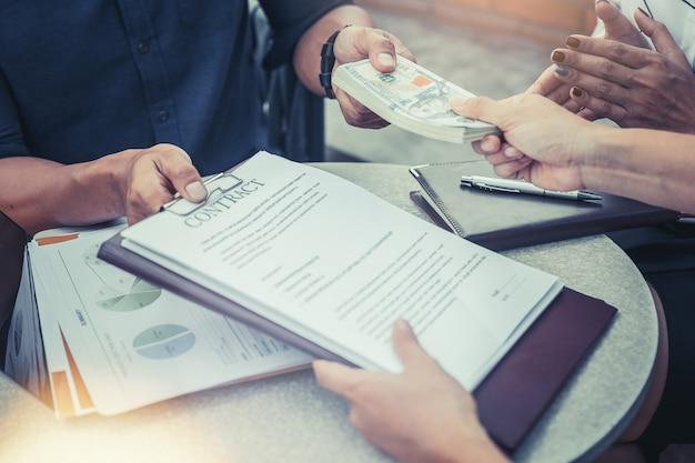 Geschäftsleute, die für zeichenvertrag sich treffen und geld zahlen. anlagekonzept