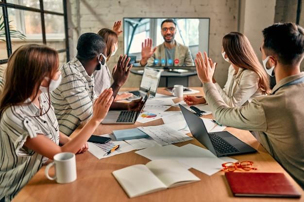 Geschäftsleute, die gesichtsmaske tragen, treffen, diskutieren, brainstorming-ideen für büroinvestitionen während des coronavirus