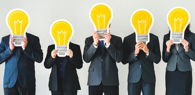 Geschäftsleute, die glühlampenikonen halten