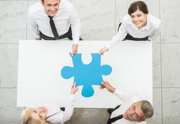 Geschäftsleute, die großes stück des puzzlespiels zusammenhalten.