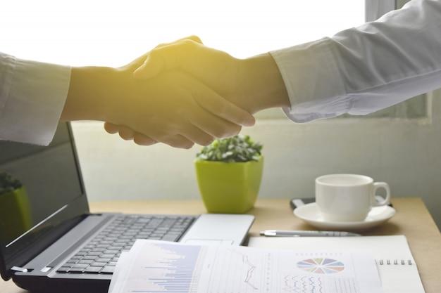 Geschäftsleute, die hände glücklich mit arbeitsvereinbarung schütteln