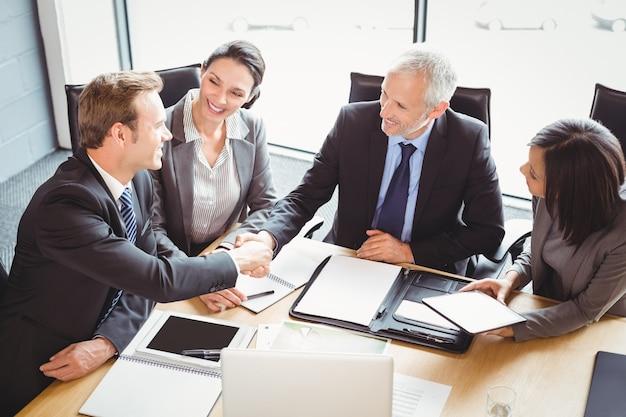 Geschäftsleute, die hände im konferenzraum rütteln