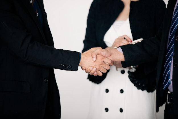 Geschäftsleute, die hände rütteln und ihre vereinbarung lächeln, vertrag zu unterzeichnen und eine sitzung oben zu beenden