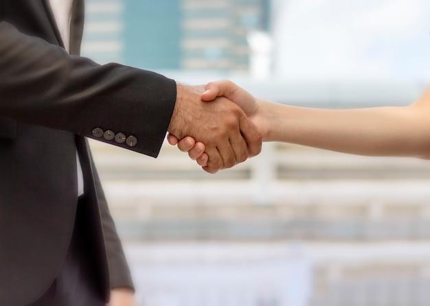 Geschäftsleute, die händedruck mit bauhintergrund machen - gruß, umgang und fusionen