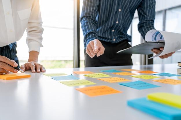 Geschäftsleute, die haftnotizen arrangieren, kommentieren und brainstorming zu kollegen mit arbeitsprioritäten in einem modernen arbeitsbereich.