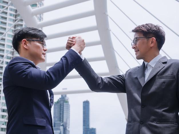 Geschäftsleute, die hand in der stadt rütteln