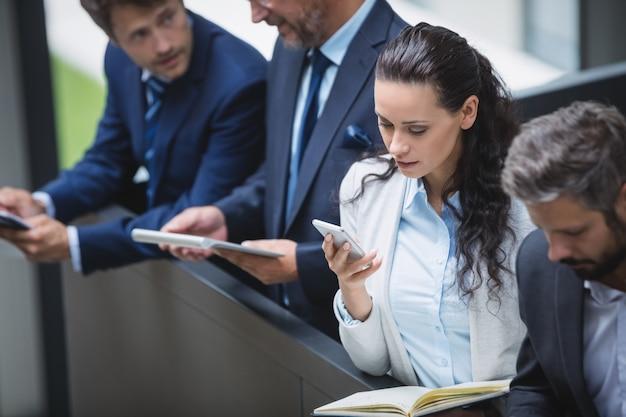 Geschäftsleute, die handy und digitales tablet verwenden