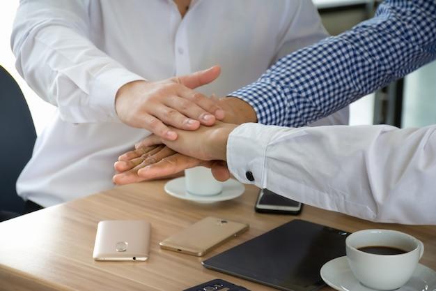 Geschäftsleute, die ihre hände auf einander auf tabelle für teamwork setzen.