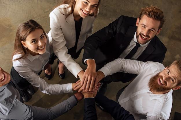Geschäftsleute, die ihre hände zusammen im büro setzen. konzept der teamarbeit und partnerschaft