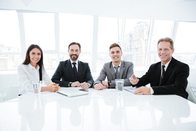 Geschäftsleute, die im büro am tisch sitzen und in die kamera schauen