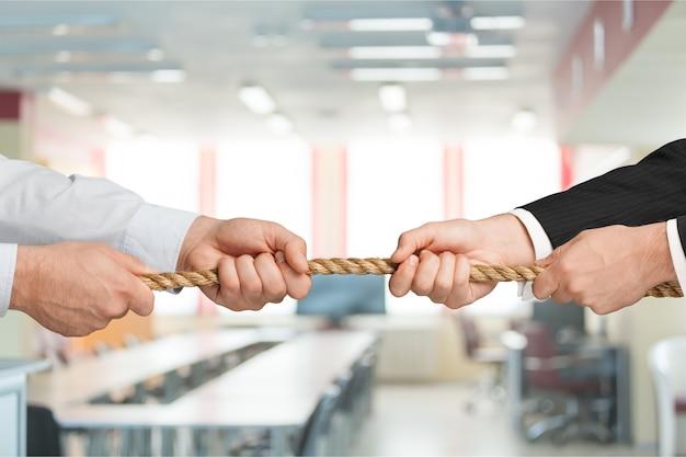 Geschäftsleute, die im büro seil in entgegengesetzte richtungen ziehen