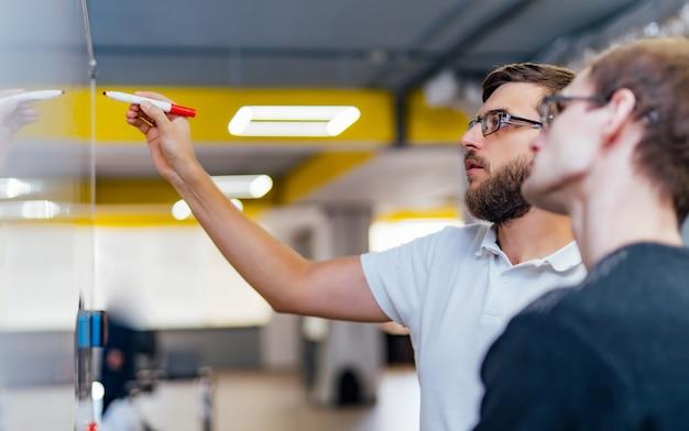 Geschäftsleute, die im büro sich treffen und verwenden post-itanmerkungen, um idee zu teilen.