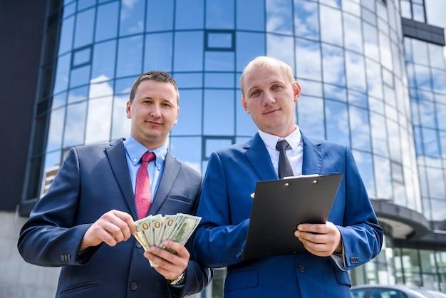 Geschäftsleute, die im freien einen vertrag mit euro-banknoten unterzeichnen